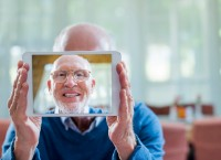 Portrait of happy senior man taking self portrait through digital tablet in nursing home
